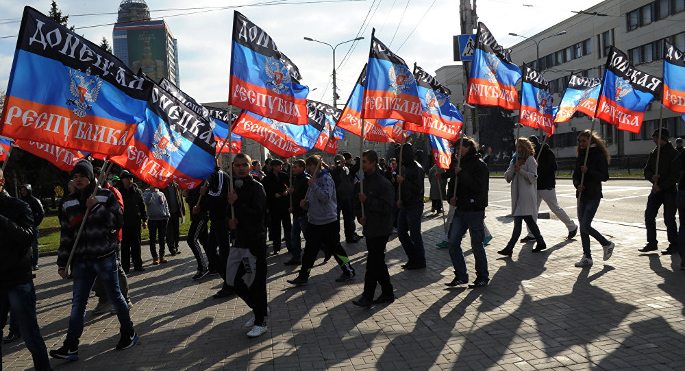 People carry flags of the self-proclaimed Donetsk People's Republic (DPR) during a ceremony for the presentation of the DPR flag at the Lenin square of Donetsk, on October 19, 2014